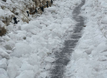 Winter path on the iced over pavement among the ice chunks Stockfoto