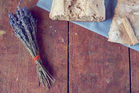 Vintage wooden background with homemade bread and bunch of dry lavender from above 스톡 콘텐츠 - 92413768