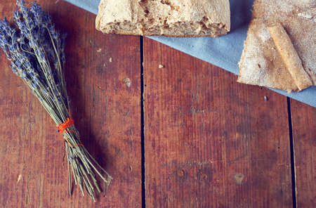 Vintage wooden background with homemade bread and bunch of dry lavender from above