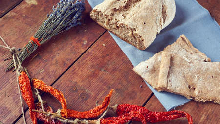 Vintage wooden background for rustic kitchen with homemade bread and bunch of lavender and red hot chili peppers Stockfoto