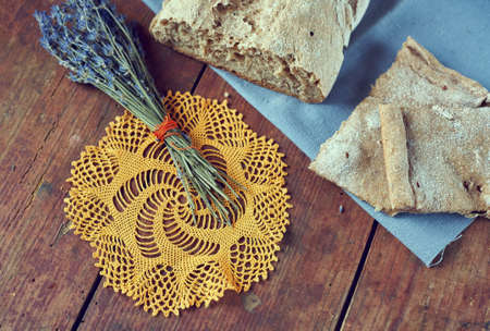 Vintage still life with homemade bread and bunch of dry lavender from above