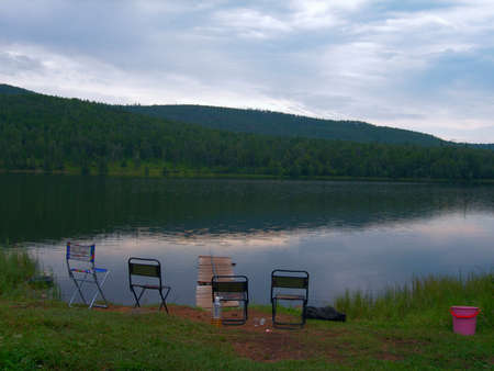 Tranquil lake view in the foreground of tourist chairs and fishing rod