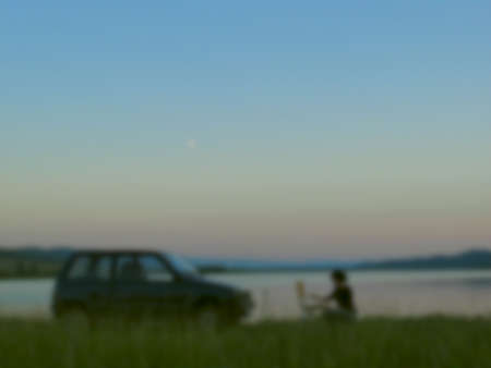 The girl artist painting on the shores of scenic lake at sunset, blurred background