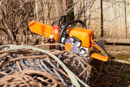 Chainsaw lies on rural bench with coils of ropes, spring season