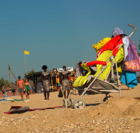 People on sandy sea beach in summer, baby buggy in the foreground 報道画像