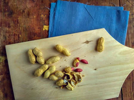 Peanuts on wooden cutting board, still life in vintage rustic style Stock Photo