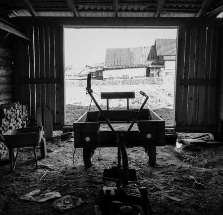 The interior is rustic barn with motor cultivator, black and white photo