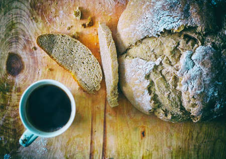 Loaf of homemade freshly baked bread and cup of coffee on the table closeup