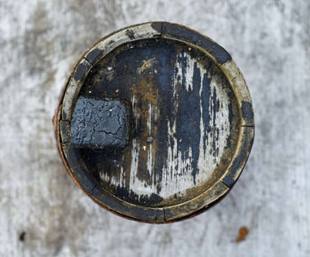 Old grimy wooden barrel for fuel oil, top view