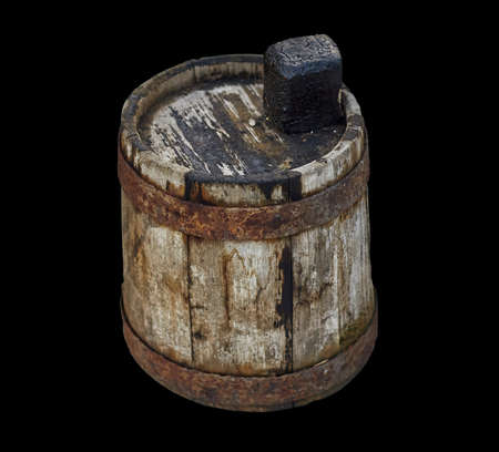 Old wooden dirty barrel for fuel oil on isolated black background closeup