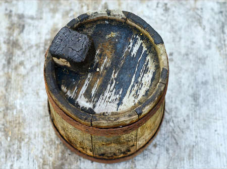 Old wooden smudgy barrel for fuel oil closeup
