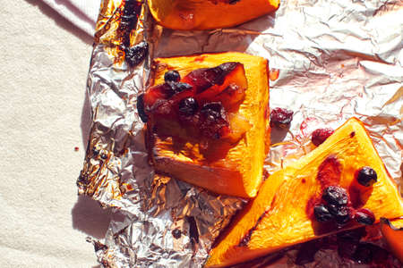 Homemade baked sweet pumpkin with cranberries traditional autumn dish close up