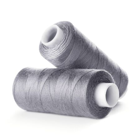 Two reels of gray thread on white background