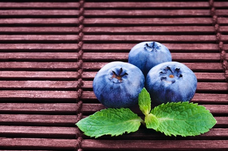 Bilberry with green mint leafs on wooden background