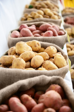 Harvest raw potatoes in burlap sack in market