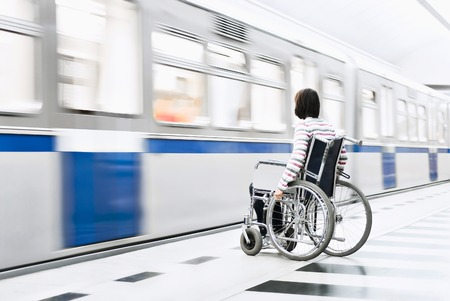invalidity: A woman in the wheelchair at the underground station Stock Photo