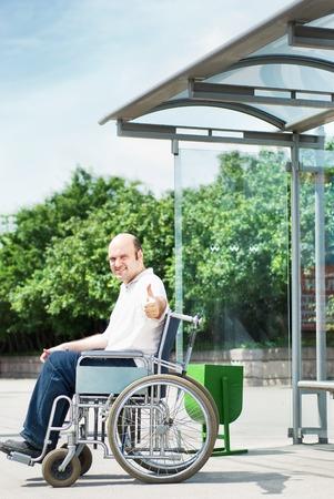 paraplegico: Hombre en una silla de ruedas en una parada de autobús