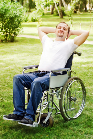 invalidity: Man in a wheelchair in the summer park