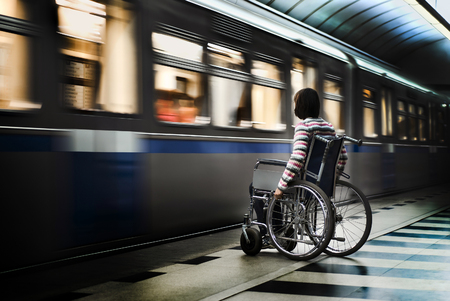 paralyze: A woman in the wheelchair at the underground station Stock Photo