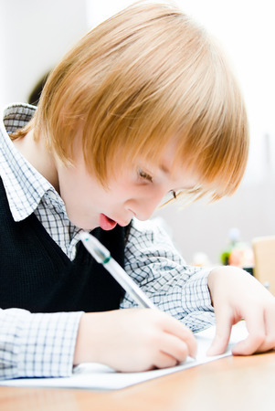 A small boy sits at the desk Stock Photo
