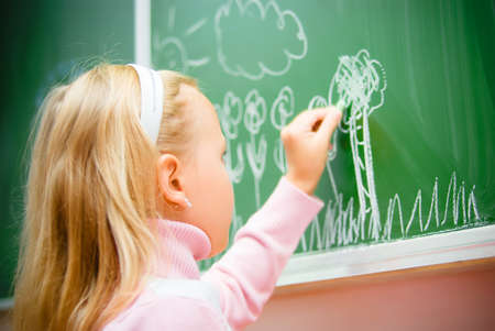 girl studying: little girl drawing on school board