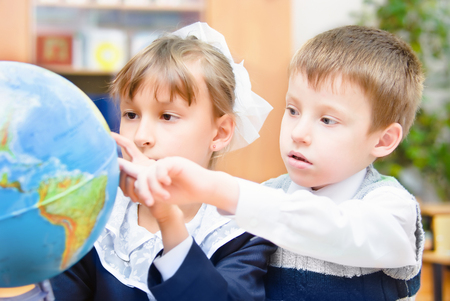 elementary age boys: Small children are studying a globe