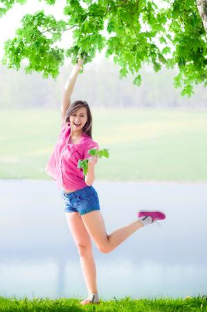 female legs: Happy beautiful girl against the lake