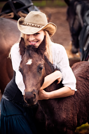 femme a cheval: Femme sexy avec un chapeau de cowboy étreint un poulain Banque d'images