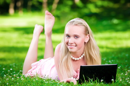 young woman smiling: Beautiful blonde on the green grass with laptop