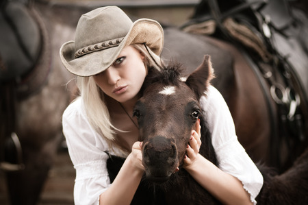 sexy blonde girl: Sexy woman with cowboy hat hugs a foal
