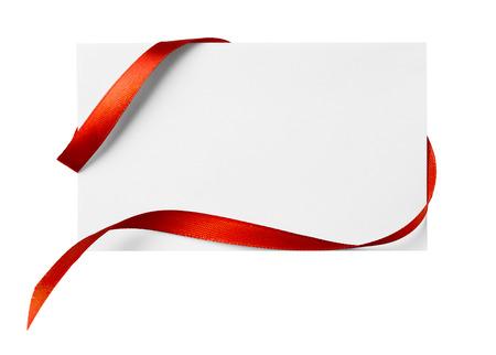 Red silk ribbon on empty paper card Foto de archivo