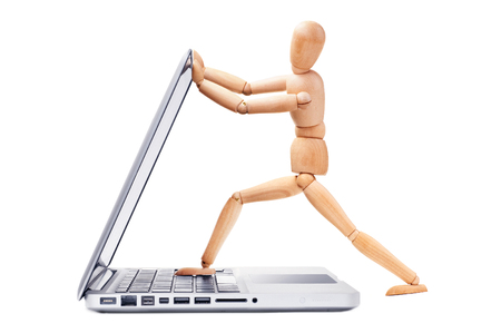 opens: Wooden man opens a laptop Stock Photo