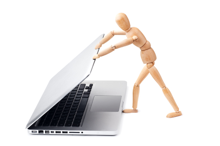 closing: Wooden man closes a laptop Stock Photo