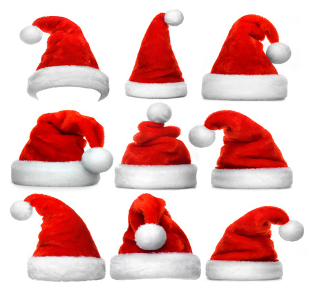 Set of red Santa Claus hats isolated on white background Фото со стока