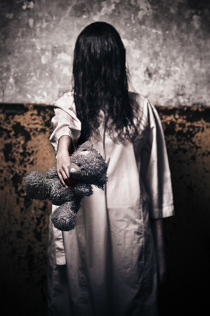 scary girl: Horror scene with girl in a white robe with a bear in his hand Stock Photo