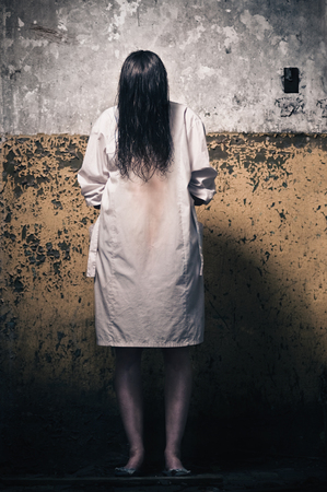 woman looking: Horror scene with girl in a white coat Stock Photo