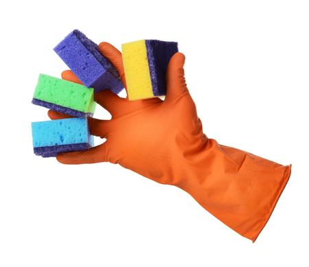 empleadas domesticas: La mano con guante de goma naranja sostiene esponjas aisladas sobre fondo blanco Foto de archivo