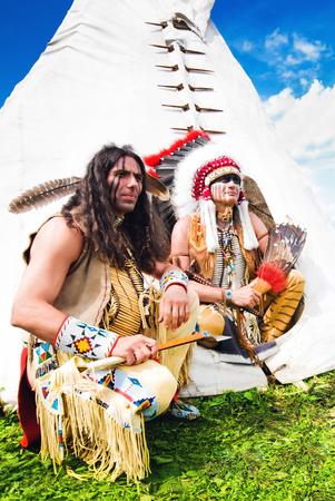 Twee indianen zitten naast wigwam Stockfoto