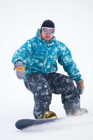 Teen snowboarder in blue jacket on the board Stok Fotoğraf - 80124778