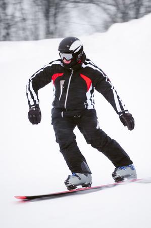 Tiener snowboarder in zwart kostuum