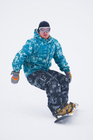 Teen snowboarder in blue jacket on the board Stok Fotoğraf - 80124774