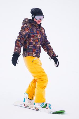 Jong meisje snowboarder in gele broek op het bord Stockfoto