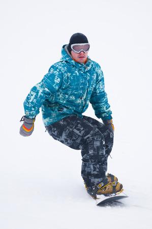 Teen snowboarder in blue jacket on the board