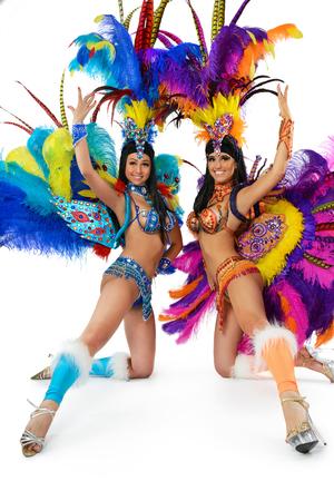 Twee glimlachende mooie meisjes in een kleurrijke carnaval kostuum