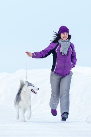 Young woman are walking with siberian husky