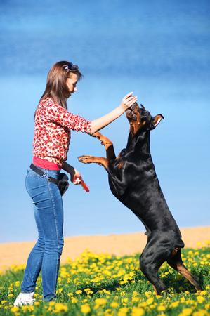 Beautiful girl playing with black dog Stok Fotoğraf