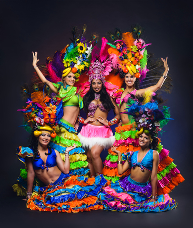 Group of young girls in bright colorful carnival costumes on dark background Фото со стока