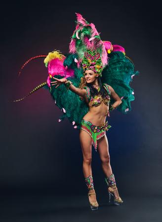 Leuk jong meisje in helder kleurrijk carnaval kostuum op donkere achtergrond