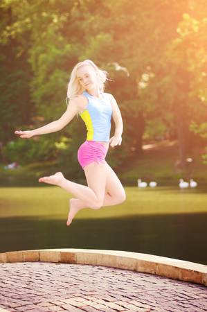 Happy girl jumping against the river