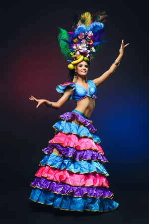 Cute young girl in bright colorful carnival costume on dark background Stock Photo